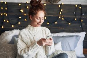 Jeune fille sur son téléphone portable assise sur son lit avec une guirlande lumineuse en fond