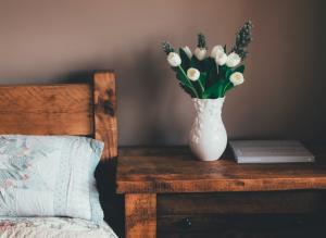 Table de chevet en bois massif avec vase de tulipes blanches dessus